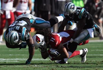 CHARLOTTE, NC - DECEMBER 19:  Larry Fitzgerald #11 of the Arizona Cardinals is tackled by teammates Captain Munnerlyn #41 and Jon Beason #52 of the Carolina Panthers during their game at Bank of America Stadium on December 19, 2010 in Charlotte, North Car