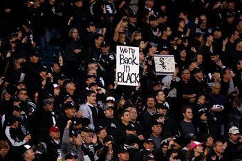 CHICAGO - SEPTEMBER 30:  A fan of the Chicago White Sox holds up a sign which reads 'We're back in black' in reference to all the fans wearing black for the game against the Minnesota Twins during the American League Central Division Tiebreaker game at U.