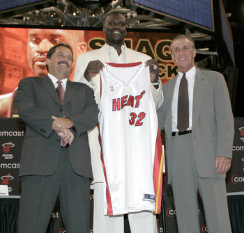 MIAMI - JULY 20:  Shaquille O'Neal of the Miami Heat holds up his new #32 jersey with Coach Stan Van Gundy (L) and Pat Riley (R) at his sides during a press conference to offically announce his arrival to the Miami Heat July 20, 2004 at the American Airli