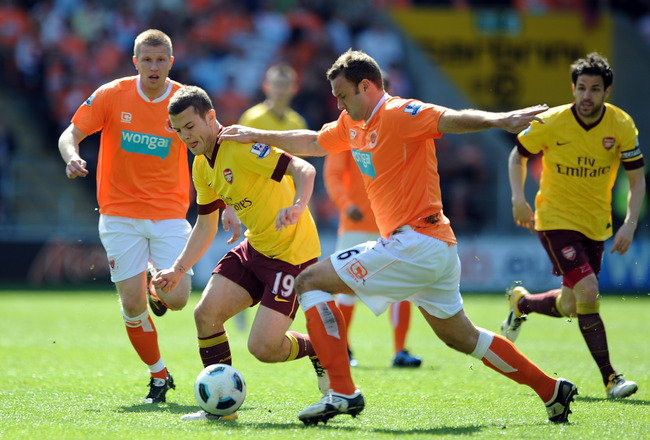 BLACKPOOL, ENGLAND - APRIL 10: Jack Wilshere of Arsenal competes with Ian Evatt of Blackpool during the Barclays Premier League match between Blackpool and Arsenal at Bloomfield Road on April 10, 2011 in Blackpool, England.  (Photo by Chris Brunskill/Gett