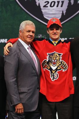 ST PAUL, MN - JUNE 24:  General Manager Dale Tallon of the Florida Panthers stands with third overall pick Jonathan Huberdeau by the Florida Panthers a Panthers jersey at the podium during day one of the 2011 NHL Entry Draft at Xcel Energy Center on June