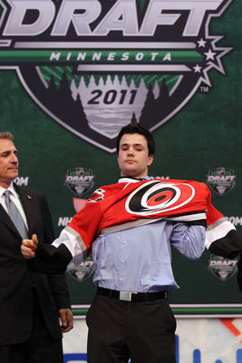 ST PAUL, MN - JUNE 24:  Twelfth overall pick Ryan Murphy by the Carolina Hurricanes puts on a Carolina Hurricanes jersey onstage during day one of the 2011 NHL Entry Draft at Xcel Energy Center on June 24, 2011 in St Paul, Minnesota.  (Photo by Bruce Benn
