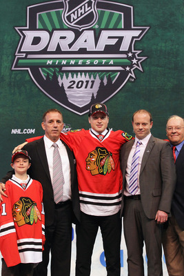 ST PAUL, MN - JUNE 24:  Eighteenth overall pick Mark McNeill by the Chicago Blackhawks stands onstage for a photo with General Manager Stan Bowman and members of the Chicago Blackhawks organization during day one of the 2011 NHL Entry Draft at Xcel Energy