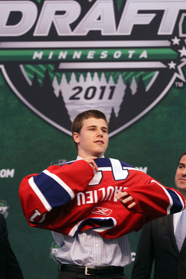 ST PAUL, MN - JUNE 24:  Seventh overall pick Nathan Beaulieu by the Montreal Canadiens stands onstage and puts on a Montreal Canadiens jersey during day one of the 2011 NHL Entry Draft at Xcel Energy Center on June 24, 2011 in St Paul, Minnesota.  (Photo