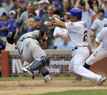 CHICAGO, IL - JUNE 18: Carlos Pena # 22 of the Chicago Cubs is tagged out at home by Russell Martin #55 of the New York Yankees on June 18, 2011 at Wrigley Field in Chicago, Illinois.  (Photo by David Banks/Getty Images)