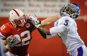 LINCOLN, NE - NOVEMBER 13: Rex Burkhead #22 of the Nebraska Cornhuskers stiff arms Greg Brown #5 of the Kansas Jayhawks during second half action of their game at Memorial Stadium on November 13, 2010 in Lincoln, Nebraska. Nebraska Defeated Kansas 20-3. (