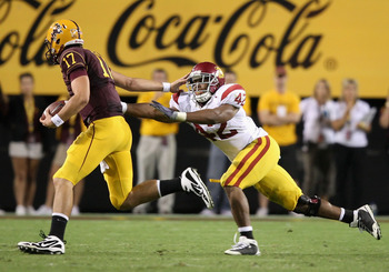 TEMPE, AZ - NOVEMBER 07:  Quarterback Brock Osweiler #17 of the Arizona State Sun Devils scrambles with the ball past Devon Kennard #42 of the USC Trojans during the college football game at Sun Devil Stadium on November 7, 2009 in Tempe, Arizona.  The Tr