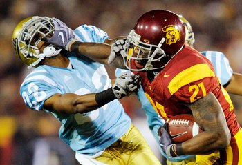 LOS ANGELES, CA - NOVEMBER 28:  Tailback Allen Bradford #21 of the USC Trojans stiff arms defensive back Sheldon Price #22 of the UCLA Bruins as he runs for a gain during the second quarter of the NCAA college football game at Los Angeles Memorial Coliseu