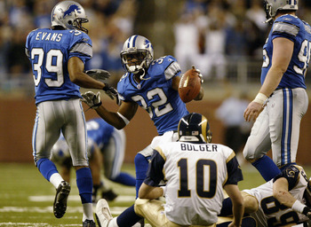 DETROIT - DECEMBER 28:  Dre Bly #32 of the Detroit Lions celebrates a fumble recovery in front of quarterback Marc Bulger #10 of the St. Louis Rams in the third quarter on December 28, 2003 at Ford Field in Detroit, Michigan.  (Photo by Harry How/Getty Im
