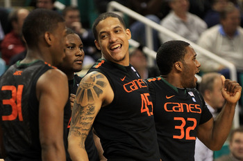 GREENSBORO, NC - MARCH 10:  Julian Gamble #45 of the Miami Hurricanes celebrates with teammates DeQuan Jones and Erik Swoope during the second half of the game against the Virginia Cavaliers in the first round of the 2011 ACC men's basketball tournament a