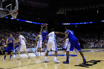 NEWARK, NJ - MARCH 27:  DeAndre Liggins #34 of the Kentucky Wildcats makes a jump shot against Kendall Marshall #5 of the North Carolina Tar Heels during the second half of the east regional final of the 2011 NCAA men's basketball tournament at Prudential