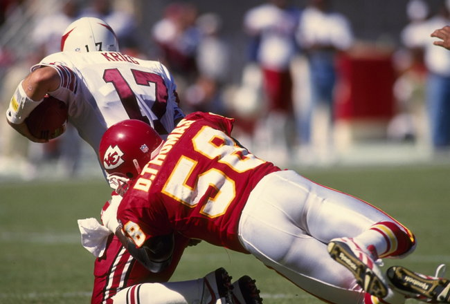 Quarterback Dave Krieg #17 of the Arizona Cardinals is hit and wrapped up by linebacker Derrick Thomas #58 of the Kansas City Chiefs during the Cardinals 24-3 loss to the Chiefs at Arrowhead Stadium in Kansas City, Missouri.