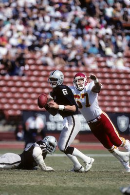 LOS ANGELES - OCTOBER 6:  Quarterback Marc Wilson #6 of the Los Angeles Raiders runs with the ball under pressure from Art Still #67 of the Kansas City Chiefs during the game at the Los Angeles Memorial Coliseum on October 6, 1985 in Los Angeles, Californ