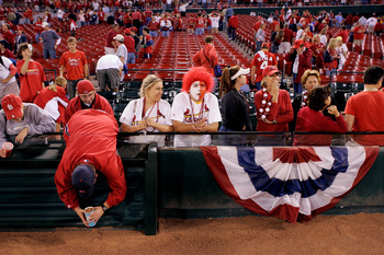 ST. LOUIS - OCTOBER 19:  Fans of the St. Louis Cardinals fills cups with dirt from the field at Busch Stadium following the Cardinals 5-1 loss against the Houston Astros during Game Six of the National League Championship Series October 19, 2005 at Busch