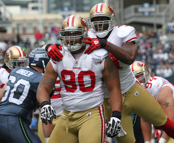 SEATTLE - SEPTEMBER 12:  Defensive tackle Isaac Sopoaga #90 of the San Francisco 49ers is congratulated by Takeo Spikes #51 after tackling Justin Forsett #20 during the NFL season opener against the Seattle Seahawks at Qwest Field on September 12, 2010 in