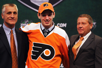ST PAUL, MN - JUNE 24:  Eighth overall pick 	Sean Couturier by the Philadelphia Flyers stands with General Manager Paul Holmgren of the Philadelphia Flyers and a member of the Philadelphia Flyers organization onstage during day one of the 2011 NHL Entry D
