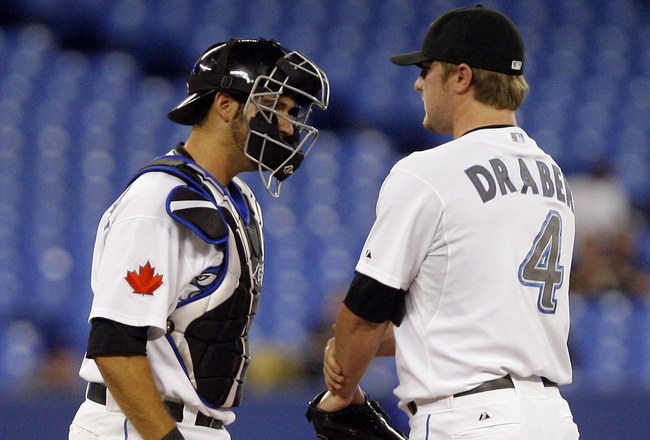 TORONTO, CANADA - MAY 10: Kyle Drabek #4 and J.P. Arencibia #9 of the Toronto Blue Jays regroup after a run against the Boston Red Sox during MLB action at the Rogers Centre May 10, 2011 in Toronto, Ontario, Canada. (Photo by Abelimages/Getty Images)