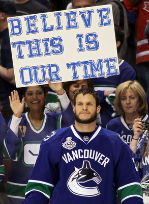 VANCOUVER, BC - JUNE 15:  Kevin Bieksa #3 of the Vancouver Canucks looks on as a Vancouver Canucks fan holds a sign that reads, 'BELIEVE THIS IS OUR TIME' prior to Game Seven against the Boston Bruins in the 2011 NHL Stanley Cup Final at Rogers Arena on J