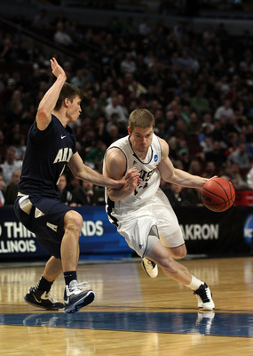 CHICAGO, IL - MARCH 18:  Scott Martin #14 of the Notre Dame Fighting Irish drives against Brett McClanahan #5 of the Akron Zips in the second half during the second round of the 2011 NCAA men's basketball tournament at the United Center on March 18, 2011