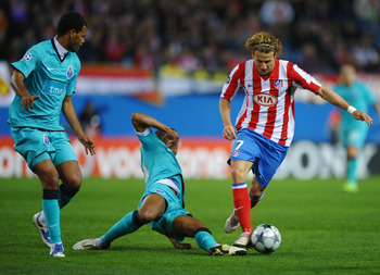 MADRID, SPAIN - FEBRUARY 24:  Diego Forlan of Atletico Madrid takes on Rolando (L) and Fernando Reges of FC Porto (C) during the Champions League Round of 16, First Leg match between Atletico Madrid and FC Porto at the Vicente Calderon on February 24, 200