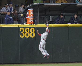 SEATTLE - JUNE 17:  Center fielder Shane Victorino #8 of the Philadelphia Phillies makes a leaping catch at the wall on a ball hit by Miguel Olivo #30 of the Seattle Mariners at Safeco Field on June 17, 2011 in Seattle, Washington. (Photo by Otto Greule J