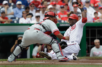 WASHINGTON, DC - JUNE 01: Roger Bernadina #2 of the Washington Nationals slides safely into homeplate to score as catcher Carlos Ruiz #51 of the Philadelphia Phillies waits for the throw during the first inning at Nationals Park on June 1, 2011 in Washing