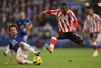 LIVERPOOL, ENGLAND - FEBRUARY 26:  Stephane Sessegnon of Sunderland leaps into a challenge for the ball with Leighton Baines of Everton during the Barclays Premier League match between Everton  and Sunderland at Goodison Park on February 26, 2011 in Liver