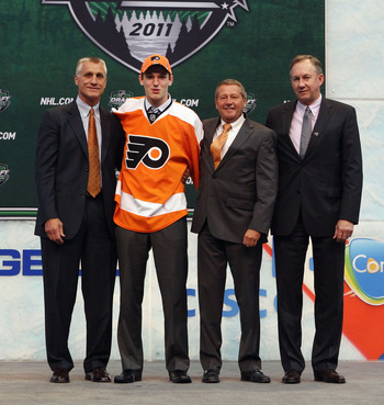 ST PAUL, MN - JUNE 24:  Eighth overall pick 	Sean Couturier by the Philadelphia Flyers stands with General Manager Paul Holmgren of the Philadelphia Flyers and members of the Philadelphia Flyers organization onstage during day one of the 2011 NHL Entry Dr