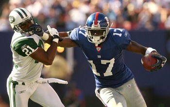 EAST RUTHERFORD, NJ - OCTOBER 07:  Plaxico Burress #17 of the New York Giants pushes off the tackle of Andre Dyson #21 of the New York Jets on his way to a touchdown in the fourth quarter at Giants Stadium on October 7, 2007 in East Rutherford, New Jersey