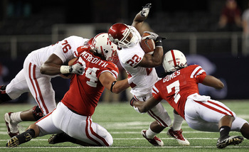 ARLINGTON, TX - DECEMBER 04:  Running back Roy Finch #22 of the Oklahoma Sooners is tackled by Cameron Meredith #34 and DeJon Gomes #7 of the Nebraska Cornhuskers during the Big 12 Championship at Cowboys Stadium on December 4, 2010 in Arlington, Texas.
