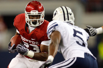 ARLINGTON, TX - SEPTEMBER 05:  Running back Jermie Calhoun #23 of the Oklahoma Sooners runs the ball past Brandon Bradley #5 of the Brigham Young Cougars of the Oklahoma Sooners at Cowboys Stadium on September 5, 2009 in Arlington, Texas.  (Photo by Ronal