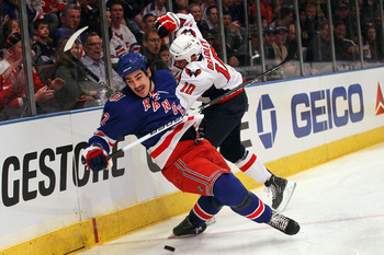 NEW YORK, NY - APRIL 17:  Brian Boyle #22 of the New York Rangers is checked by Matt Bradley #10 of the Washington Capitals in Game Three of the Eastern Conference Quarterfinals during the 2011 NHL Stanley Cup Playoffs at Madison Square Garden on April 17