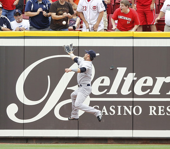 CINCINNATI, OH - JUNE 22:  Nick Swisher #33 of the New York Yankees jumps to catch a fly ball near the outfield wall during the game against the Cincinnati Reds at Great American Ball Park on June 22, 2011 in Cincinnati, Ohio. The Yankees defeated the Red