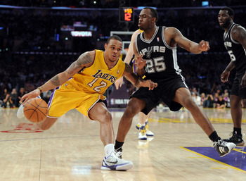 LOS ANGELES, CA - APRIL 12:  Shannon Brown #12 of the Los Angeles Lakers dribbles on James Anderson #25 of the San Antonio Spurs during the game at Staples Center on April 12, 2011 in Los Angeles, California.  NOTE TO USER: User expressly acknowledges and