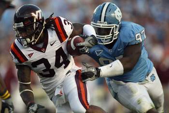 CHAPEL HILL, NC - NOVEMBER 13:  Ryan Williams #34 of the Virginia Tech Hokies is tackled by Jared McAdoo #97 of the North Carolina Tar Heels during their game at Kenan Stadium on November 13, 2010 in Chapel Hill, North Carolina.  (Photo by Streeter Lecka/