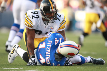 ORCHARD PARK, NY - NOVEMBER 28:  James Harrison #92 of the Pittsburgh Steelers rises after hitting Ryan Fitzpatrick of the Buffalo Bills during their game at Ralph Wilson Stadium on November 28, 2010 in Orchard Park, New York.  Harrison was flagged for ro