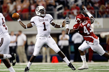 ARLINGTON, TX - OCTOBER 03:  Quarterback Jerrod Johnson #1 of the Texas A&M Aggies drops back to pass against Tenarius Wright #43 of the Arkansas Razorbacks at Dallas Cowboys Stadium on October 3, 2009 in Arlington, Texas.  (Photo by Ronald Martinez/Getty
