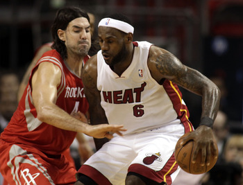 MIAMI, FL - MARCH 27:  Forward LeBron James #6  of the Miami Heat battles against Forward Luis Scola #4 of the Houston Rockets  at American Airlines Arena on March 27, 2011 in Miami, Florida. NOTE TO USER: User expressly acknowledges and agrees that, by d