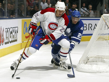 TORONTO - OCTOBER 8:  Alexander Khavanov #25 of the Toronto Maple Leafs tries to get between the net and Alex Kovalev #27 of the Montreal Canadiens during their NHL game at the Air Canada Centre October 8, 2005 in Toronto, Ontario. The Canadiens beat the