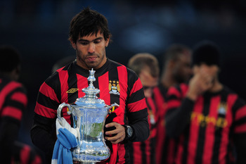 MANCHESTER, ENGLAND - MAY 23:  Carlos Tevez of Manchester City lifts the FA Cup tduring the Manchester City FA Cup Winners Parade at the City of Manchester stadium on May 23, 2011 in Manchester, United Kingdom.  (Photo by Jamie McDonald/Getty Images)