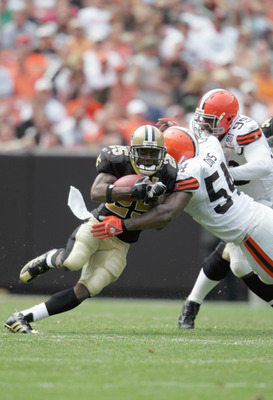 CLEVELAND - SEPTEMBER 10:  Running back Reggie Bush #25 of the New Orleans Saints grips the ball as he is tackled during the game against the Cleveland Browns at Cleveland Browns Stadium on September 10, 2006 in Cleveland, Ohio. The Saints defeated the Br