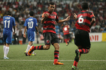 KALLANG, SINGAPORE - JUNE 24: (SINGAPORE OUT ) Arlindo Neto #9 of CR Flamengo runs to congratulate goal scorer Jorge Marco #6  during the 2011 Canon Lion City Cup semi final match between Singapore U-15 and CR Flamengo at Jalan Besar Stadium on June 24, 2