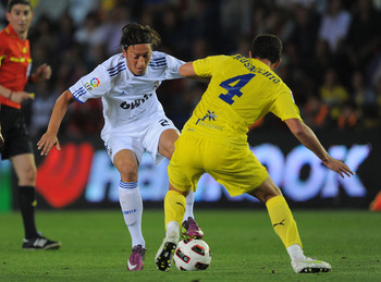 VILLARREAL, SPAIN - MAY 15: Mesut Ozil (L) of Real Madrid takes on Mateo Musacchio of Villarreal during the La Liga match between Villarreal and Real Madrid at estadio El Madrigal on May 15, 2011 in Villarreal, Spain.  (Photo by Denis Doyle/Getty Images)
