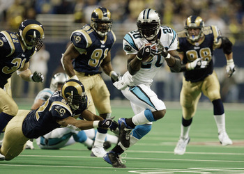 ST. LOUIS - JANUARY10:  Running back DeShaun Foster #20 of the Carolina Panthers attempts to evade linebacker Tommy Polley #52 of the St. Louis Rams during the NFC Divisional Playoff game on January 10, 2004 at the Edward Jones Dome in St. Louis, Missouri