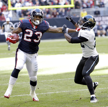 HOUSTON - JANUARY 02:  Running back Arian Foster #23 of the Houston Texans gives Don Carey #22 of the Jacksonville Jaguars a stiff arm at Reliant Stadium on January 2, 2011 in Houston, Texas.  (Photo by Bob Levey/Getty Images)