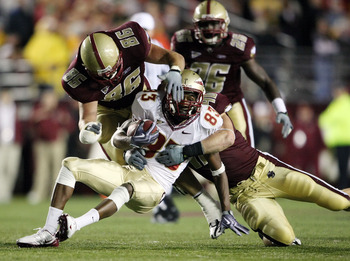 CHESTNUT HILL, MA - OCTOBER 03:  Bert Reed #83 of the Florida State Seminoles is tackled by Jim Ramella #86 and Luke Kuechley #40 of the Boston College Eagles on October 3, 2009 at Alumni Stadium in Chestnut Hill, Massachusetts. Boston College defeated Fl