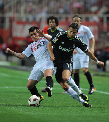 SEVILLE, SPAIN - MAY 07: Gary Medel (L) of Sevilla tackles Cristiano Ronaldo of Real Madrid during the La Liga match between Sevilla and Real Madrid at Estadio Ramon Sanchez Pizjuan on May 7, 2011 in Seville, Spain.  (Photo by Denis Doyle/Getty Images)