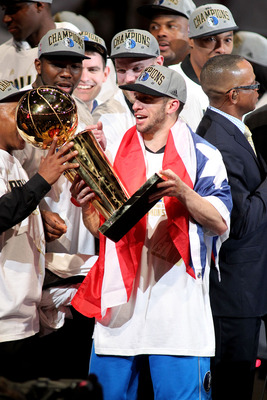 MIAMI, FL - JUNE 12:  Jose Juan Barea #11 of the Dallas Mavericks celebrates with the Larry O'Brien Championship trophy after the Mavericks won 105-95 against the Miami Heat in Game Six of the 2011 NBA Finals at American Airlines Arena on June 12, 2011 in