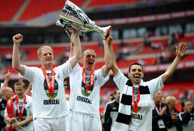 LONDON, ENGLAND - MAY 30: Garry Monk of Swansea (c) lifts the trophy as they celebrate promotion to the Premier League with Alan Tate (l) and Leon Britton during the npower Championship Playoff Final between Reading and Swansea City at Wembley Stadium on