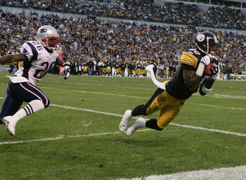 PITTSBURGH - OCTOBER 31:  Split end Plaxico Burress #80 of the Pittsburgh Steelers makes a catch near cornerback Eugene Wilson #26 of the New England Patriots during the game at Heinz Field on October 31, 2004 in Pittsburgh, Pennsylvania. The Steelers def